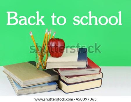 Back to school image of a stack of old, worn books with a fresh red apple and a jar full of brand new pencils on a white table with a bright green background. Text added.