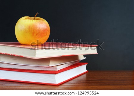 Back to school. Image of blank teacher's desk with a pile of textbooks and apple - stock photo