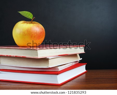Back to school. Image of teacher's desk with a pile of textbooks and apple