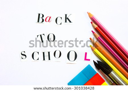 Back to School Letters cut out from the Magazine with colourful pencils, brushes and stickers nearby - stock photo