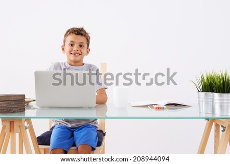 Back to School. Little boy using his laptop - stock photo