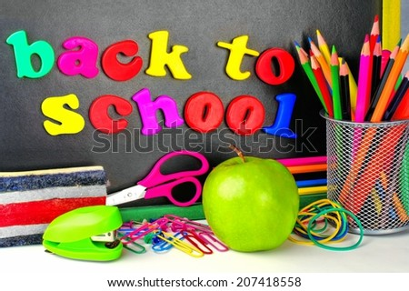 Back To School magnetic letters on a blackboard with school supplies - stock photo