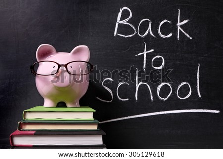 Back to school message memo reminder, chalk blackboard, piggy bank, education costs and saving concept - stock photo