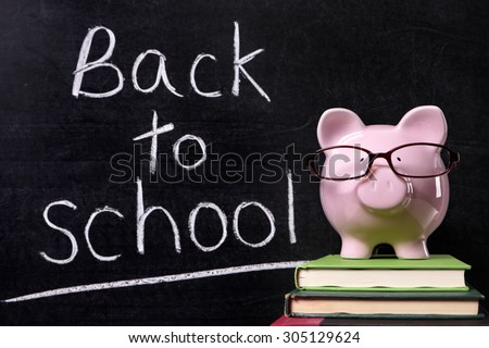 Back to school message reminder, classroom blackboard, piggy bank - stock photo