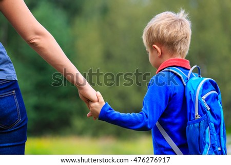 back to school - mother holding hand of little son