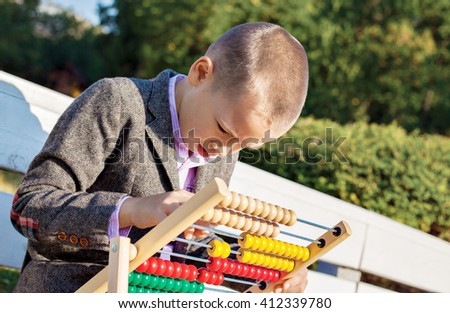 Back to school one little boy counting and playing on wooden abacus in the park.  - stock photo