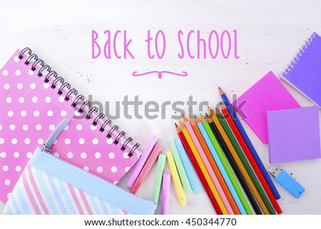 Back to School or Education Concept with stationery and desk accessories overhead on white wood rustic table with added filteres and retro hand drawn style text. - stock photo