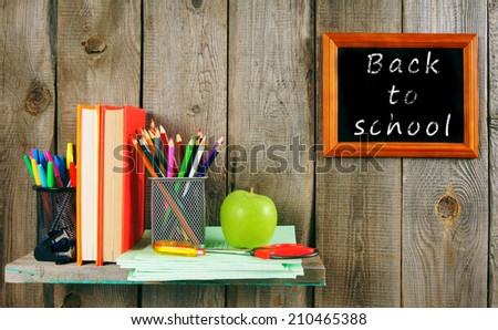 Back to school. School accessories on a wooden shelf. A wooden background.