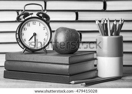 Back to school, school books with apple on desk. Old style, black - white photo.