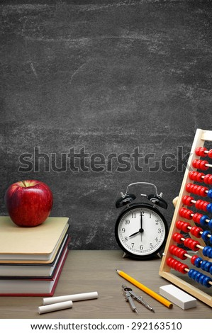 Back To School / School Supplies, an Apple and an Alarm Clock on a Desk in front of a Blackboard - stock photo