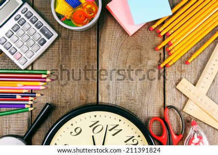 Back to school. School tools around. Vertically. A wooden background. - stock photo