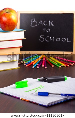 Back to school sign on a blackboard with books and apple