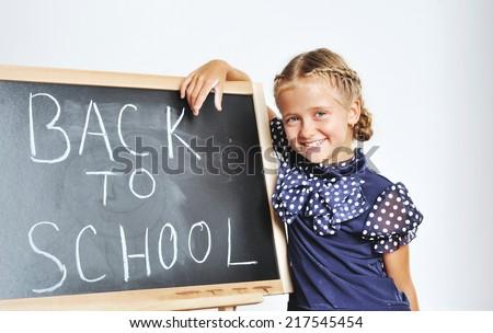 Back to school. Smiling cute school girl drawing on blackboard - stock photo