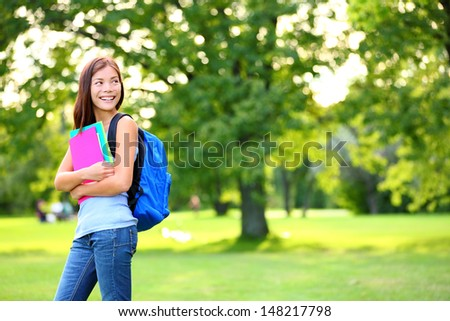Back to school student girl looking to side in park holding books and note books wearing backpack. Female university college student looking at copyspace in park. Beautiful young multiracial woman. - stock photo
