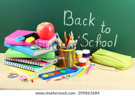 Back to school supplies. Books and blackboard. - stock photo