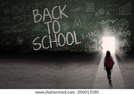 Back to school: Text of back to school on the blackboard with a door on the board - stock photo