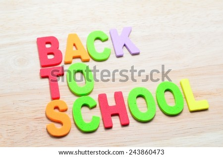 Back to School text with shadow on wooden background