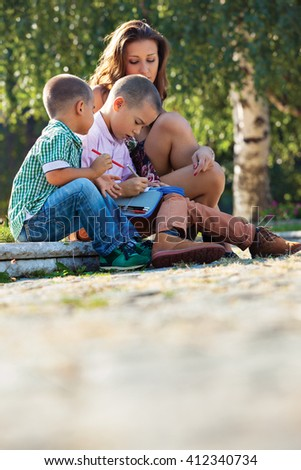 Back to school - two  little boys studying lesons in the summer or spring park with their mother.