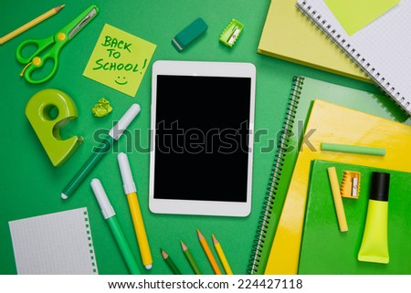 Back to school with digital tablet and green stationery on desktop. - stock photo