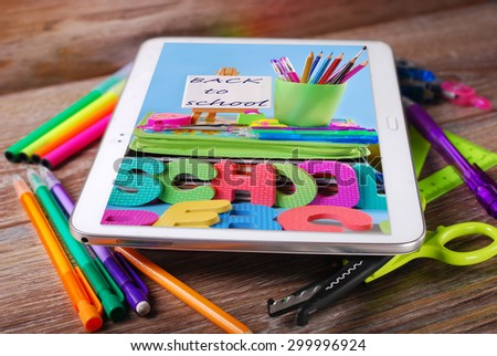 back to school wooden background with tablet pc displaying photo of colorful tools - stock photo