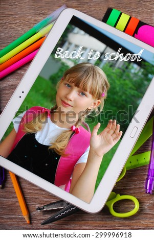 back to school wooden background with tablet pc displaying photo of happy school girl and text