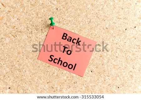 back to school word typed on a paper and pinned to a cork notice board