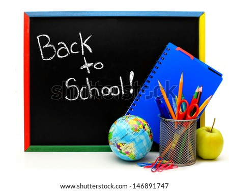 Back to School written on a blackboard with school supplies