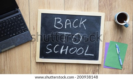 Back to school written on a chalkboard at the office - stock photo