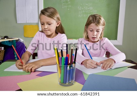 Back to school - 8 year old school girls in classroom writing in notebook