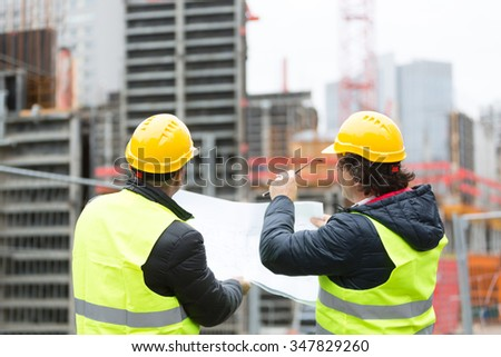 Back turned architect and technician at construction site reviewing office blueprints - stock photo