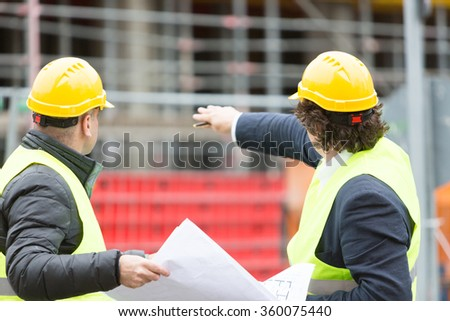 Back turned construction workers with yellow hardhat and safety jacket checking office blueprint - stock photo