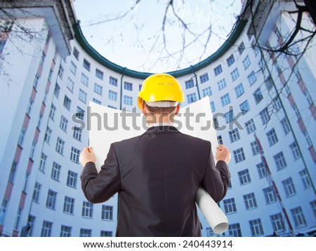 Back view architect look comparing blue print paper plan document housing project with building yellow helmet businessman stand round building many windows  background                                - stock photo