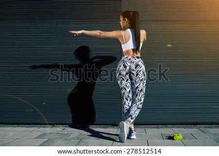 Back view athletic woman with perfect figure and buttocks shape exercising against wall with copy space for your text message, fit female in sportswear working out stretching on background outdoors - stock photo
