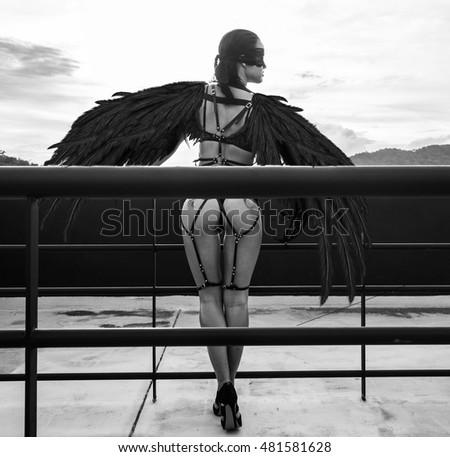 Back view black and white photo of beautiful seductive angel woman with covered eyes wearing lingerie and leather belts standing on the roof over cloudy sky