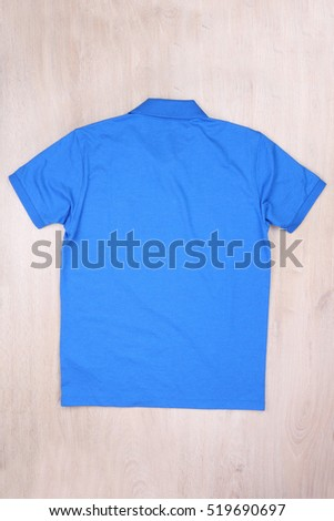Back view blue polo shirt on wooden background