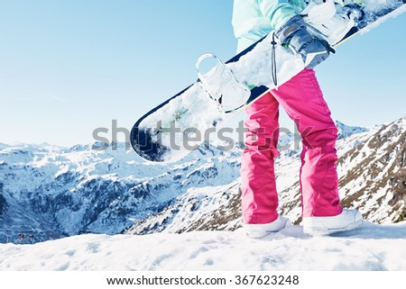 Back view close up of female snowboarder wearing blue jacket, grey gloves and pink pants standing with snowboard in one hand and enjoying sunny alpine mountain landscape - snowboarding concept - stock photo