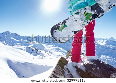 Back view close up of female snowboarder wearing helmet, blue jacket, grey gloves and pink pants standing with snowboard in one hand and enjoying alpine mountain landscape - winter sports concept