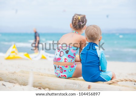Back view cute 2 years old boy with his sister looking at kiting on tropical beach