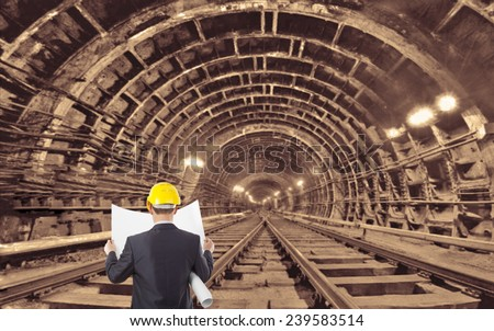 Back view engineer hand holding yellow helmet for workers security and blueprint paper plan against the background of an underground mine with arc legs and rails for trolleys with coal in perspective - stock photo