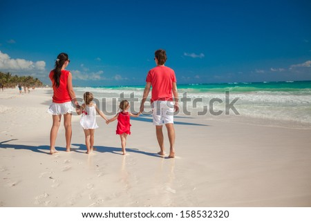 Back view family of four on beach vacation - stock photo