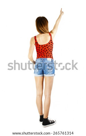 Back view Full length of young slim tanned female in denim shorts pointing at blank copy space, isolated on white background - stock photo