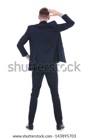 back view full length picture of a young business man standing with a hand on his hip and scratching his head with the other. on white background
