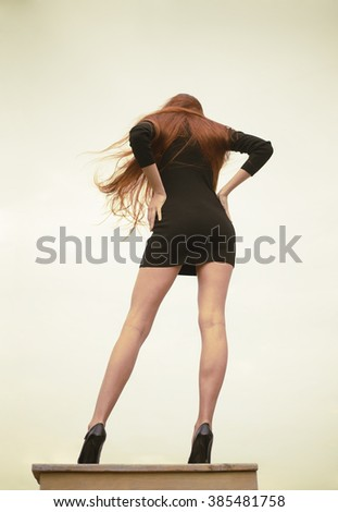 Back view. Glamour full length of a fashionable beautiful redhead woman. Outdoor over blue sky background. Young adult woman wear short black sexy dress. Tall girl with long red hair and legs - stock photo