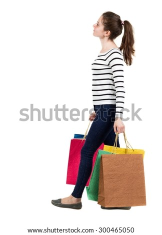 back view going  woman  with shopping bags . beautiful girl in motion. backside view of person. Isolated over white background. Frenchwoman in the vest goes right with shopping bags and looking upward - stock photo