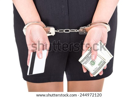 Back view, hands of young woman is holding a lot of money and credit card, on white background.  A handcuffs on her hands. - stock photo