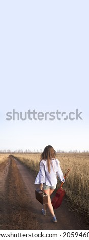 Back view hippie Woman walking in golden wheat field with acoustic Guitar on his shoulder and old retro suitcase in the other hand Empty Copy space for inscription - stock photo