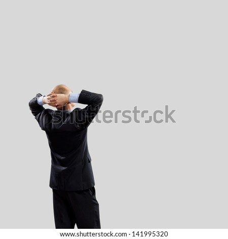 Back view image of businessman with arms crossed behind head. Place for text - stock photo