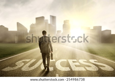 Back view male manager with briefcase walking on the road to success in the morning - stock photo