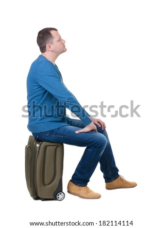 back view man sitting on a suitcase. waiting at the station. backside view of person.  Rear view people collection. Isolated over white background. guy with travel bag on wheels looking at something  - stock photo