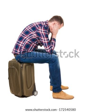 back view man sitting on suitcase. waiting at station. backside view person.  Rear view people collection. Isolated over white background. guy with a travel bag on wheels looking at something at top - stock photo